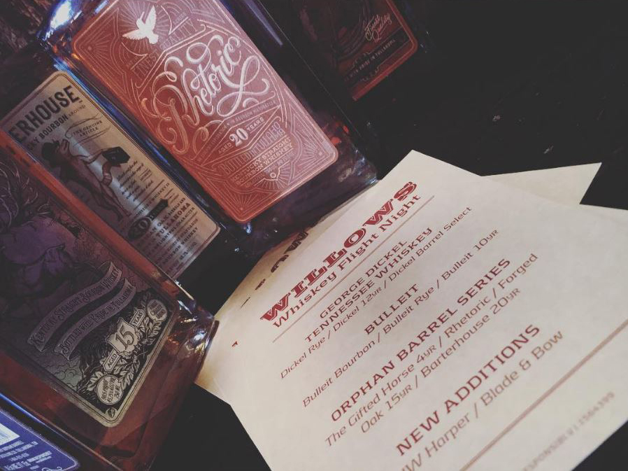 Photo of drink menu and whiskey bottles at The Willows bar in San Francisco